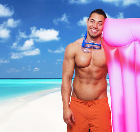 Smiling muscular male with pink water matress posing on a beach.