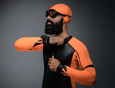 scubadiving: Portrait of bearded male in scuba diving mask and orange neopren diving suit isolated on grey background.