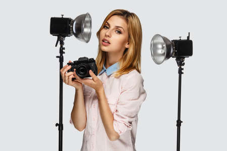 Studio portrait of positive blond female with photo camera with photo equipment on background. Stock Photo