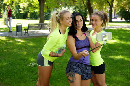 workouts: Three sporty females doing selfie in a park after fitness workouts.
