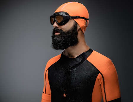 Close up portrait of bearded male in scuba diving mask and orange neopren diving suit isolated on grey background.