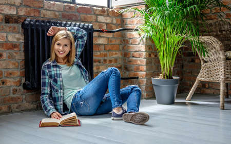 living wisdom: Attractive casual blond female sitting on the floor and reading a book in living room.