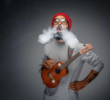 ciggy: Bearded unformal male holding acoustic small guitar and smoking a cigarette.