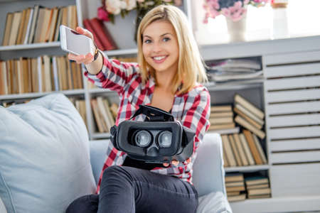 livingroom: Smiling blond female showing virtual reality glasses in a living room.