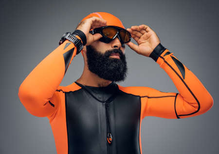 Portrait of bearded male in scuba diving mask and orange neopren diving suit isolated on grey background.