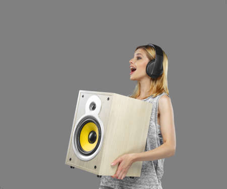 subwoofer: Portrait of blond female in earphones holding subwoofer. Isolated on grey background.