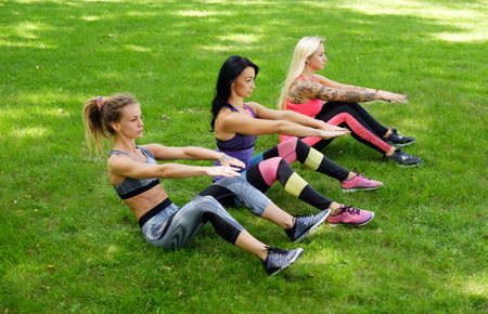 workouts: Three sporty females doing abs workouts on green lawn in a park.