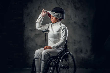 safety mask: Portrait of female fencer in wheelchair with safety mask and rapier on grey background.