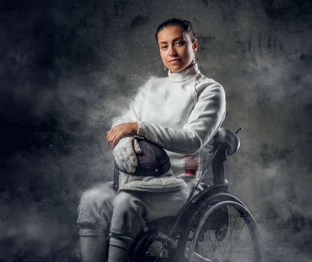 safety mask: Female fencer in wheelchair with safety mask of a face holding rapier, dust effect on image. Stock Photo