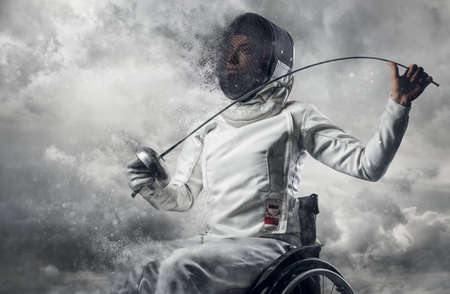 Female fencer in wheelchair with safety mask of a face, holding rapier on cloudy sky background.
