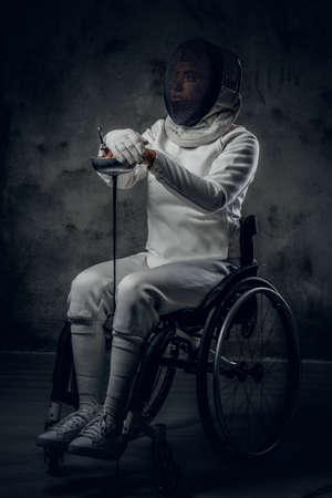esgrimista: Retrato de esgrima en silla de ruedas femenina. Foto de archivo