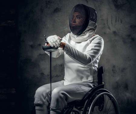 Female fencer in wheelchair with safety mask on a face. Stock Photo