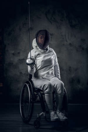 rapier: Studio portrait of paralympic female fencer in wheelchair.