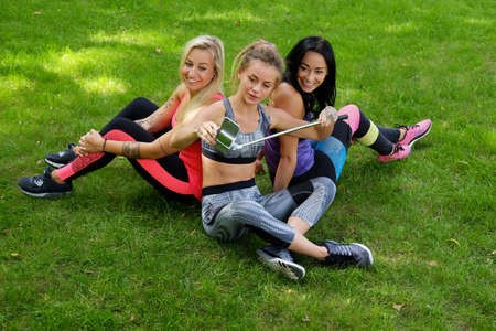 workouts: Three attractive sporty females sitting on a lawn and doing selfie after fitness workouts.