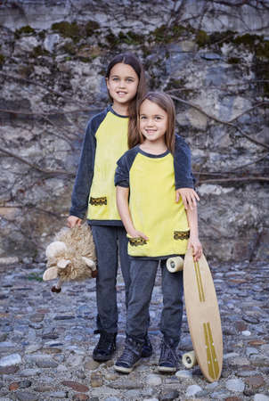 plushy: Two cute teenage females with skateboard and plushy toy posing over natural grey background. Stock Photo