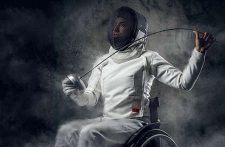 rapier: Female fencer in wheelchair with safety mask on a face holding rapier, dust effect on image.