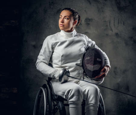 esgrimista: Female paralympic wheelchair fencer in studio.