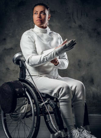 Studio portrait of paralympic female fencer in wheelchair.