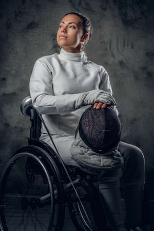rapier: Portrait of female fencer in wheelchair with safety mask and rapier on grey background.