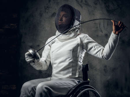 safety mask: Female fencer in wheelchair with safety mask on a face. Stock Photo