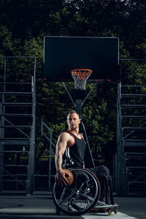 Cripple basketball player in wheelchair holding ball on open ground.
