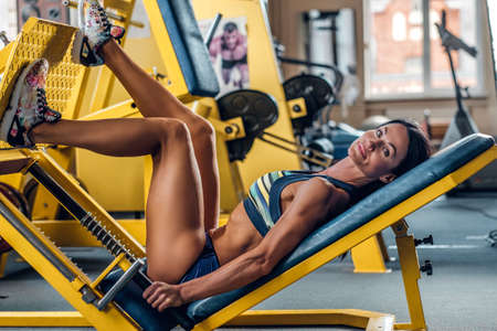 Suntanned fitness female model lying on legs workout machine in a gym club. Stock Photo