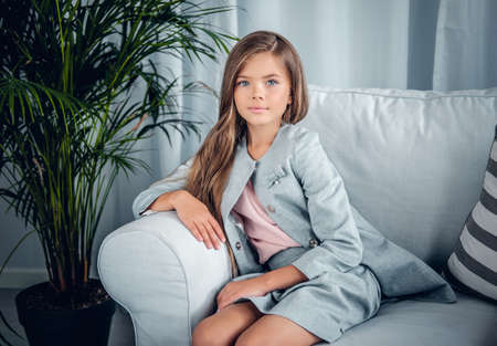 Portrait of a girl posing on a sofa in a living room with green plants.
