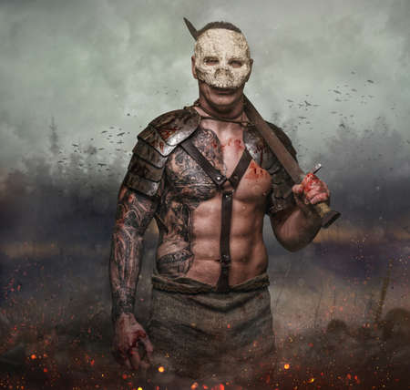 skull mask: Brutal artistic male in the skull mask holds sword in the dust batterfield background. Stock Photo
