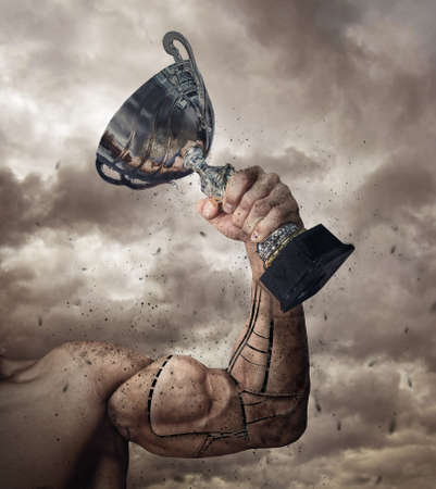Human arm prosthesis with winner cup on cloudy sky background.