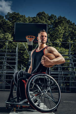 Portrait of cripple basketball player in wheelchair on open gaming ground.