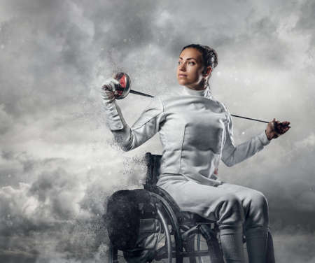 Female fencer in wheelchair with safety mask of a face holding rapier on cloudy sky background.