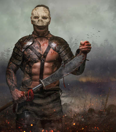 Brutal artistic male in the skull mask holds sword in the dust batterfield background. Stock Photo