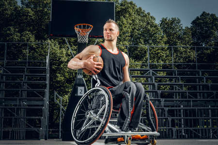 musculine: Portrait of cripple basketball player in wheelchair on open gaming ground.