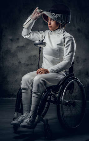 Portrait of female fencer in wheelchair with safety mask and rapier on grey background.