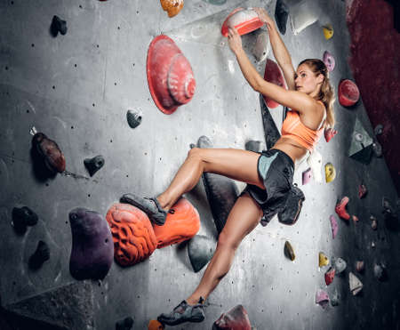 Athletic female climbing on a climbing wall with light effect on the image.