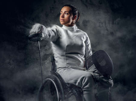 Female fencer in wheelchair with safety mask of a face holding rapier, dust effect on image. Stock Photo