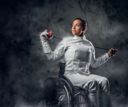 rapier: Female fencer in wheelchair with safety mask of a face holding rapier, dust effect on image. Stock Photo