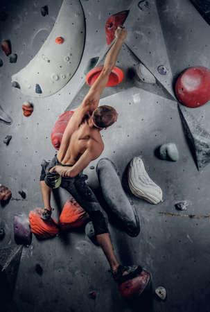 rockclimbing: Shirtless sporty male climbing on an indoor climbing wall.