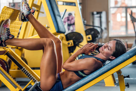 suntanned: Suntanned fitness female model lying on legs workout machine in a gym club. Stock Photo