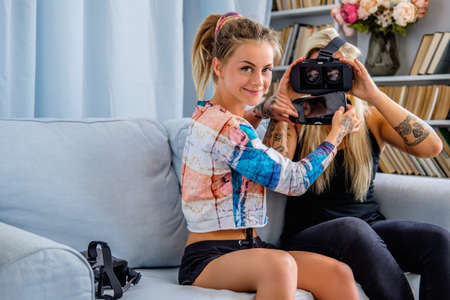 Two sexy females having fun with virtual reality glasses device at home. Stock Photo