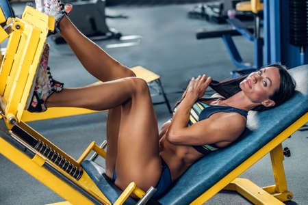 female legs: Suntanned fitness female model lying on legs workout machine in a gym club. Stock Photo