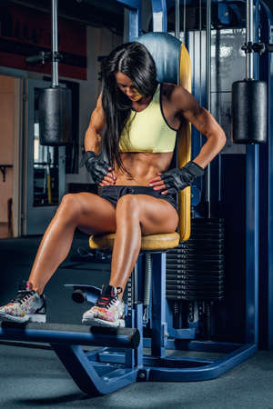 Suntanned fitness female exercising on multi action machine in a gym club.