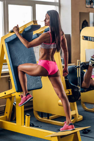 suntanned: Suntanned fitness female doing workouts on legs exercising machine in a gym.