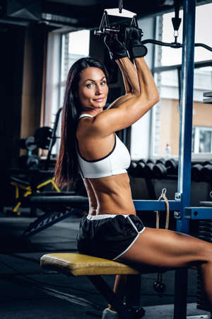 Portrait of muscular female doing workouts on exercising machine.
