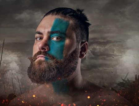 Artistic close up portrait of Scandinavian male warrior on a battlefield.