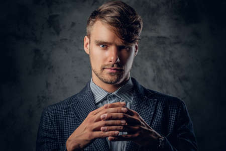 managing money: Studio portrait of modern, stylish male on glance grey background.