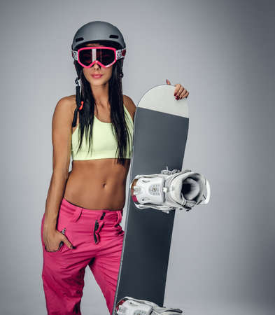 suntanned: Smiling brunette female in a pink snowing pants and green t shirt holding snowboard isolated on grey background.