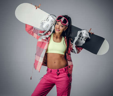 suntanned: Positive brunette female holding a snowboard on her shoulder in a studio on grey background Stock Photo