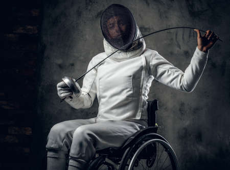 rapier: Female fencer in wheelchair with safety mask of a face, holding rapier on grey background. Stock Photo
