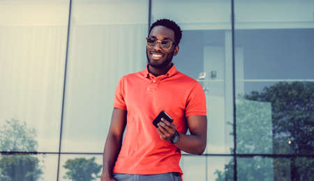 red shirt: Smiling African American male in sunglasses and red shirt using a smartphone. Stock Photo